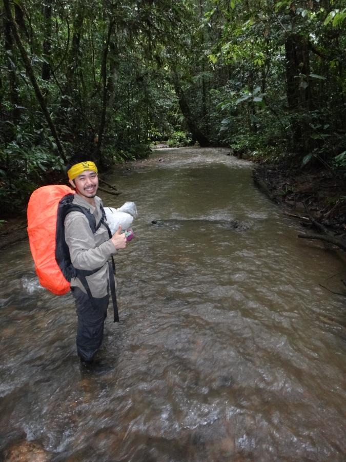 Seth wading through a stream