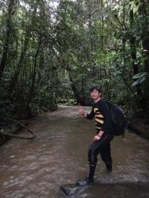 Nick wades through a forest stream